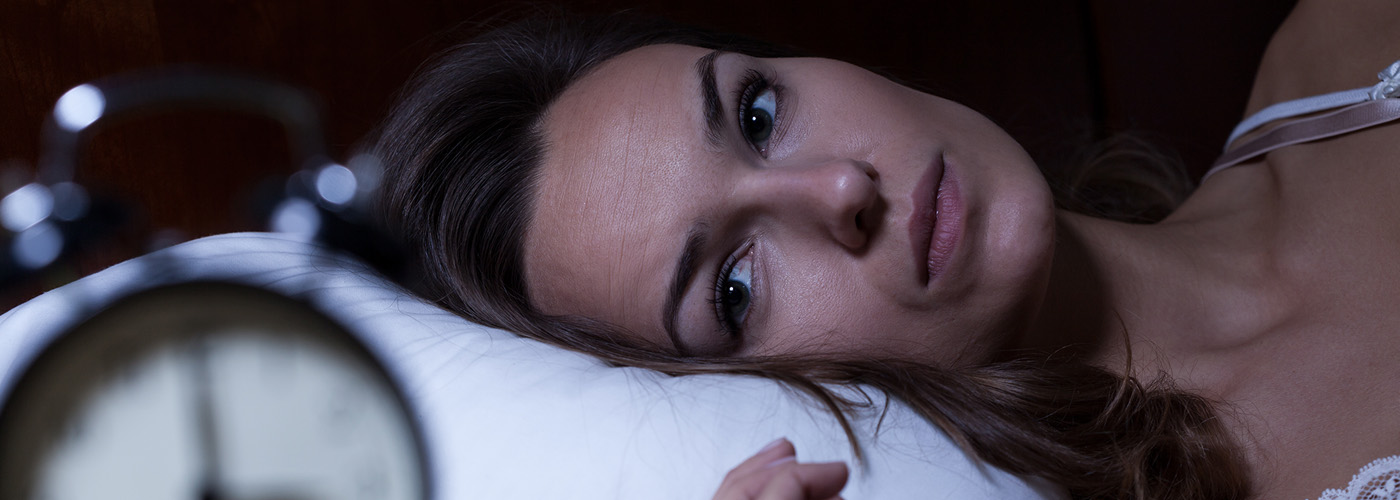 Woman trying to sleep looking at alarm clock