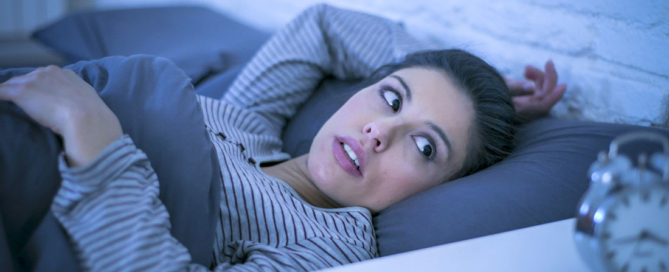 a woman stares at an alarm clock in bed