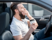 Driving man yawns holding coffee in Jacksonville