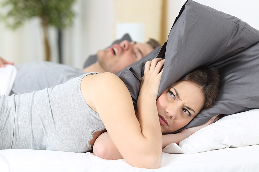 woman covering her ears while her husband snores