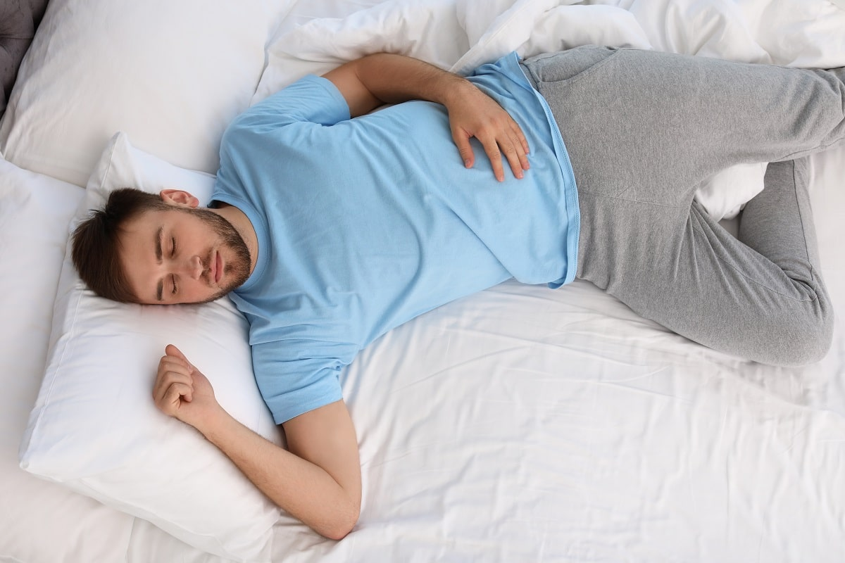 Man sleeping with fist clenched.
